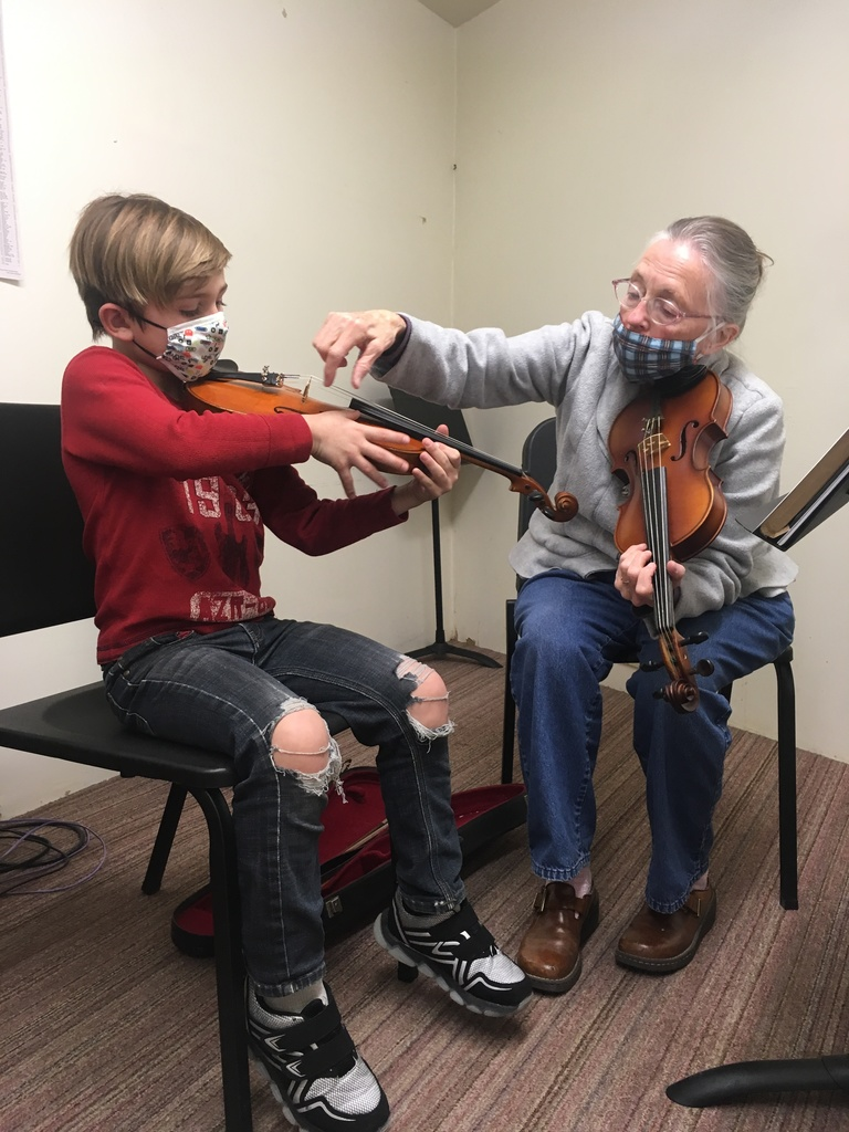student receiving instruction in violin
